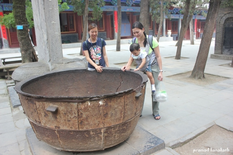 Visitors taking a curious look at a giant vessel used to prepare food for monks in the ancient times.